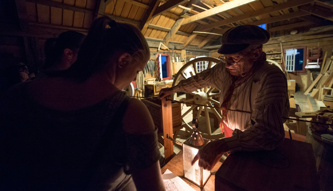 Photograph of a volunteer carpenter dressed in an 1840s work shirt and hat speaking to a female visitor inside the Carpenter Shop during a nighttime special event.