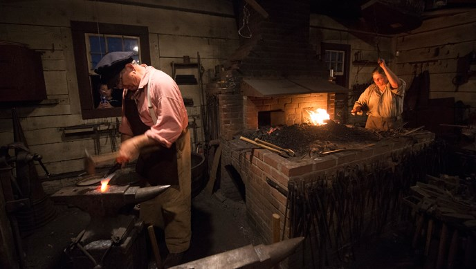 Photo of volunteer blacksmiths at work in the Blacksmith shop at nighttime; one on the left is hammering at an anvil and one on the right is working at a hot forge.