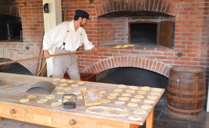 Costumed baker loads sea biscuit into the oven at the fort's Bake House