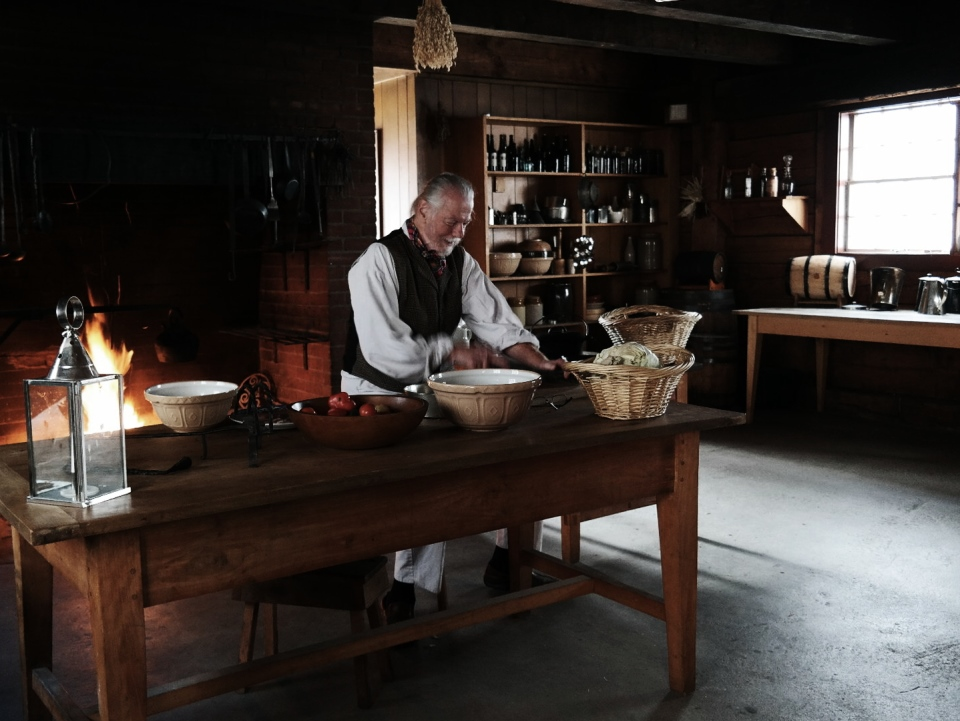 Volunteer dressed in period clothing in the reconstructed fort's kitchen.