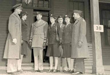 Photo of Military Men and Women standing on the porch of the Women's Army Corps barracks