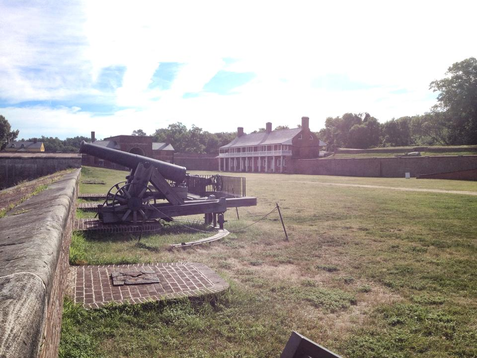 A 24lb cannon on a carriage on the fort wall on a sunny day.