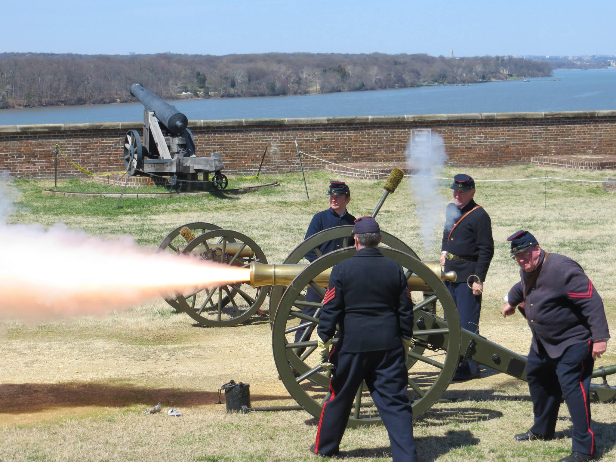 Park staff and volunteers in Civil War uniforms firing a cannon.