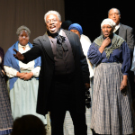 A man in historical clothing sings with a group of backup singers
