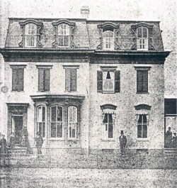 A black-and-white photograph of Frederick Douglass standing in front of a home