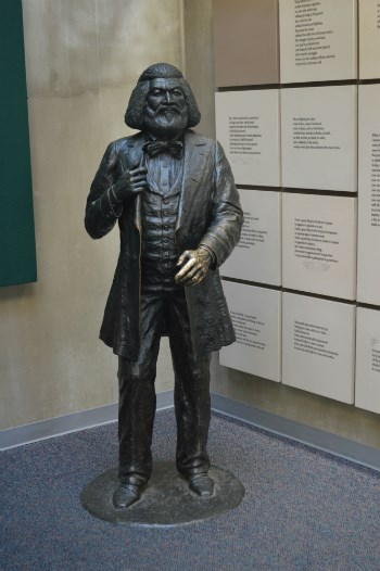 A statue of Frederick Douglass standing next to text panels