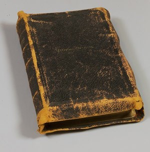 "A worn leather-bound Bible embossed with ""Frederick Douglass"" on the cover."