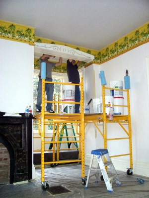 Two men stand on scaffolding and apply wallpaper to a room