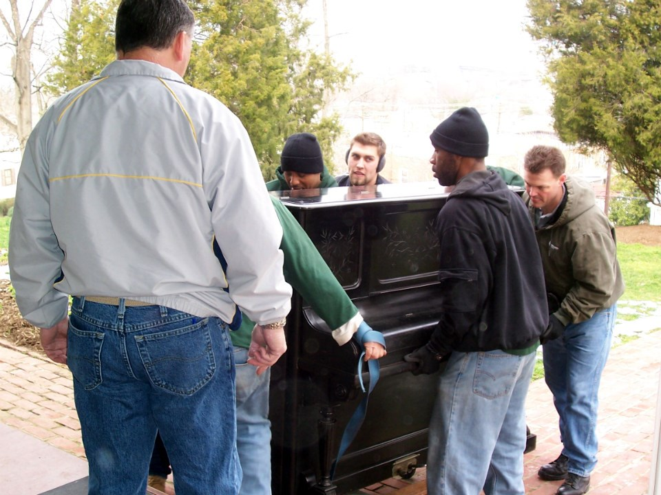 A crew carries an old upright piano