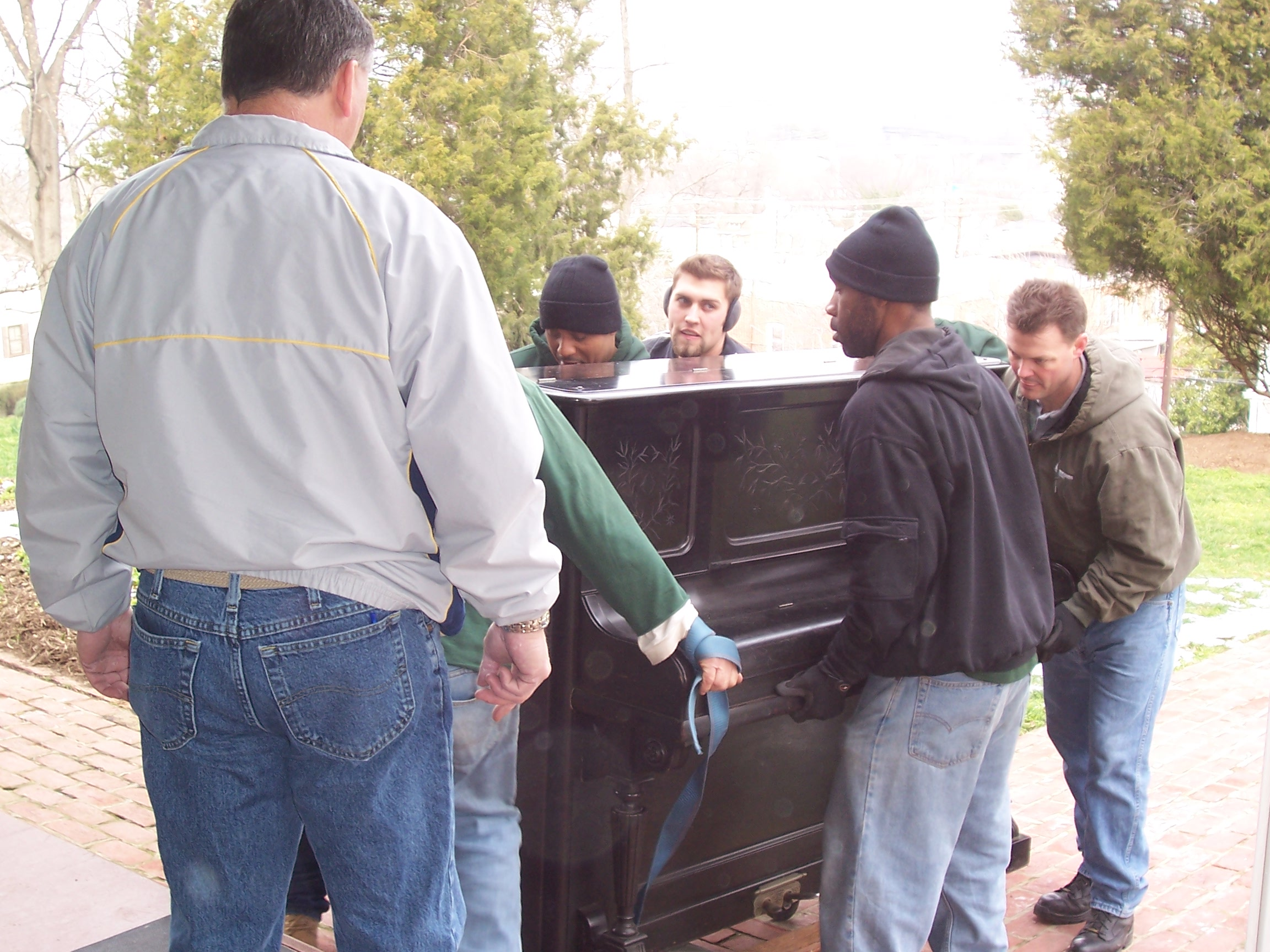 Movers move Frederick Douglass' piano back into the house.