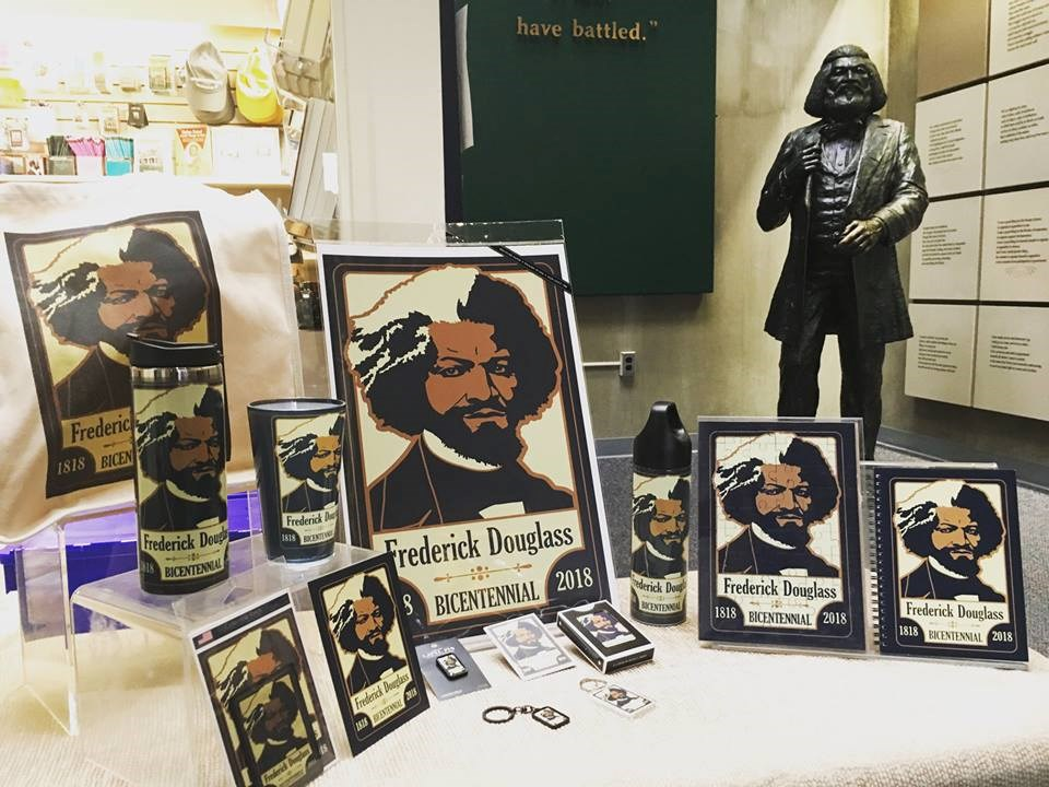 A table with posters, puzzles, coffee mugs, and other items featuring a logo with Frederick Douglass on it