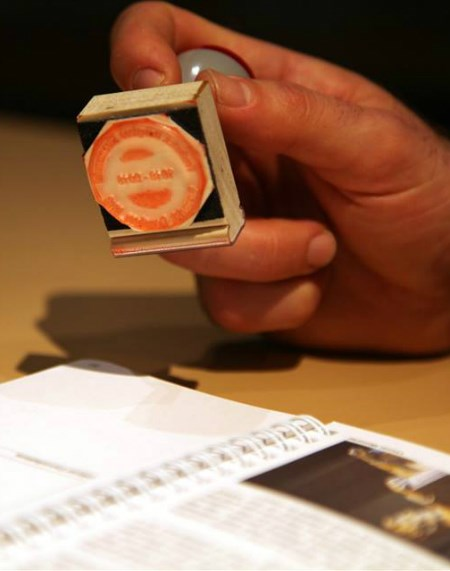A hand holding a stamp over a booklet