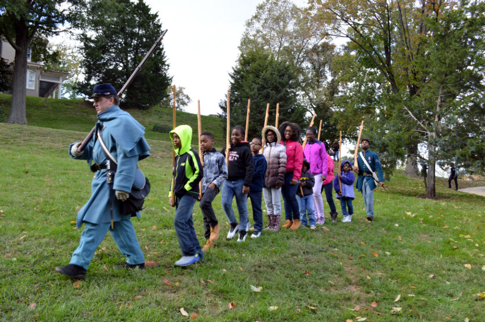 A line of children with wooden rifles follow a man dressed in a Civil War uniform