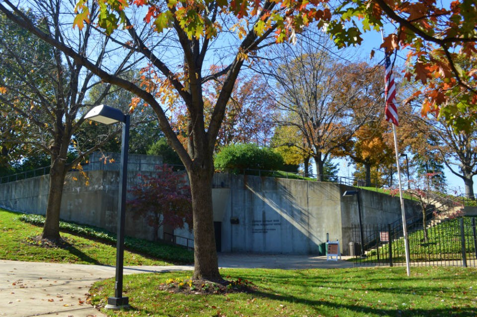 A concrete building surrounded by trees with fall foliage