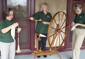 Volunteers spinning and carding wool