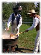 Men in historic clothing stirring soup in a cast iron pot