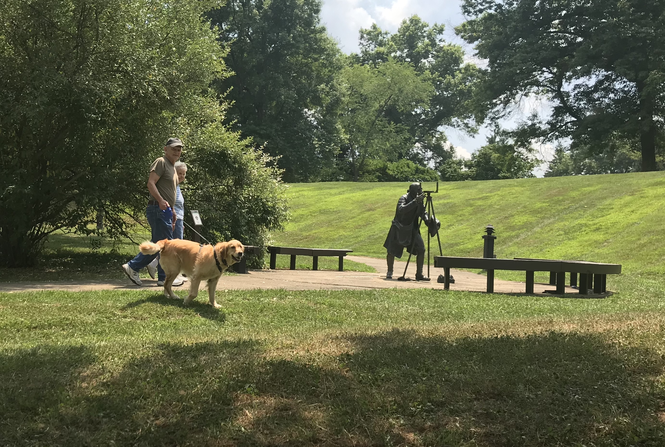 Couple hiking with dog near statue of Albert Gallatin