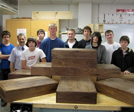 Woodworking students and teacher pose with finished boxes