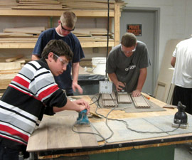 Woodworking students sanding wood