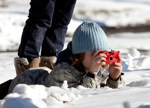 Youth taking photos in a winter landscape
