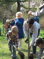 NPS staff, interns, and local students plant a new elm as a crowd watches.