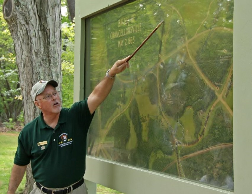 Volunteer leading a guided walking tour at Chancellorsville by pointing out features on a large battle painting