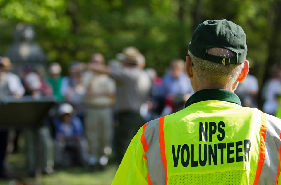 Volunteer in yellow traffic vest helping with special event