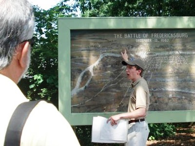 Intern begins guided walking tour beside large battle painting at Fredericksburg