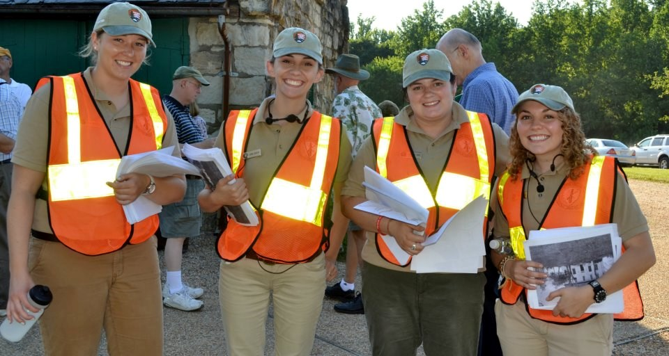 Four interns in orange traffic vests assist with a special program