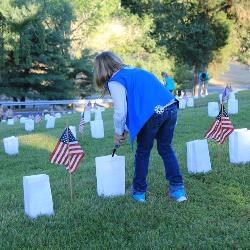 A girl scout lights a luminary candle in the Fredericksburg National Cemetery with American flags on the graves