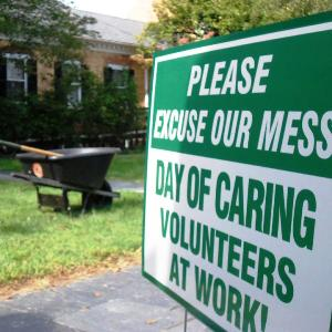 "Sign reading ""Please Excuse our Mess: Day of Caring Volunteers at Work!"" with wheelbarrow in background in gardens at Chatham Manor"