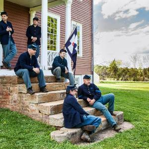 Six living history volunteers in Union uniforms relax on the front steps of Ellwood Manor