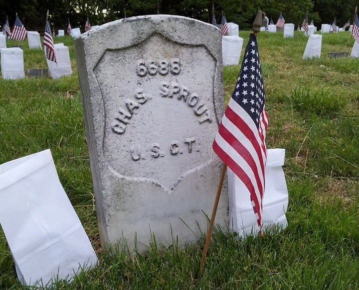 Grave of Charles Sprout in National Cemetery with American flag and two luminaries flanking stone