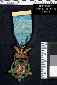 Medal of Honor attached to blue ribbon with ruler shown for scale