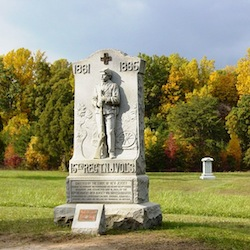 Monument in front of rolling landscape  and treeline with fall foliage