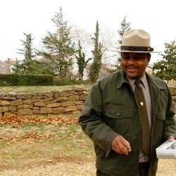 Park Ranger standing on Sunken Road with modern houses in background