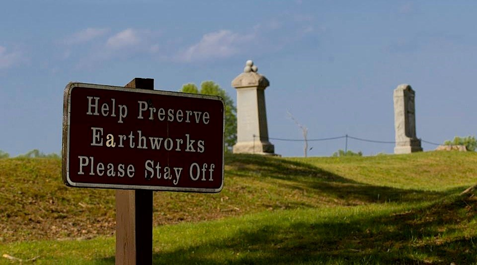 "Earthworks at Bloody Angle with two monuments in background and sign reading ""Help Preserve Earthworks Please Stay Off"" in foreground"