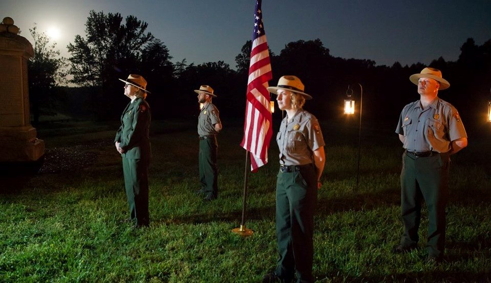 Four park historians stand as silent sentinels around an American flag at the Bloody Angle at night with the moon overhead