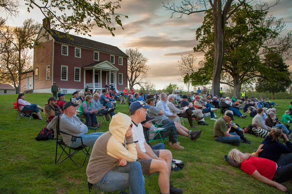Visitors gather for an evening program with Ellwood Manor in background