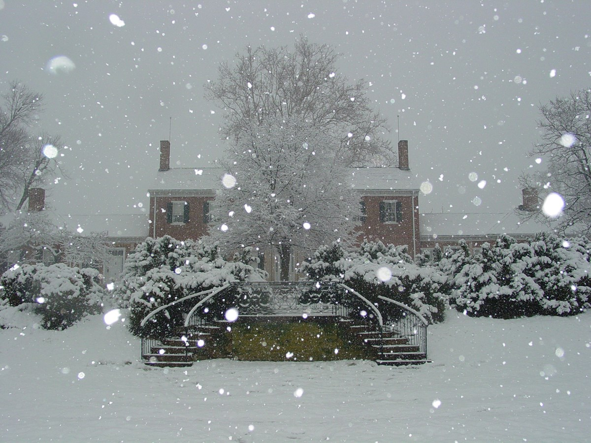 Large brick house with steps leading up to terraces during snow storm