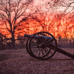 Cannon at Prospect Hill on the Fredericksburg battlefield illuminated by bright red sunset