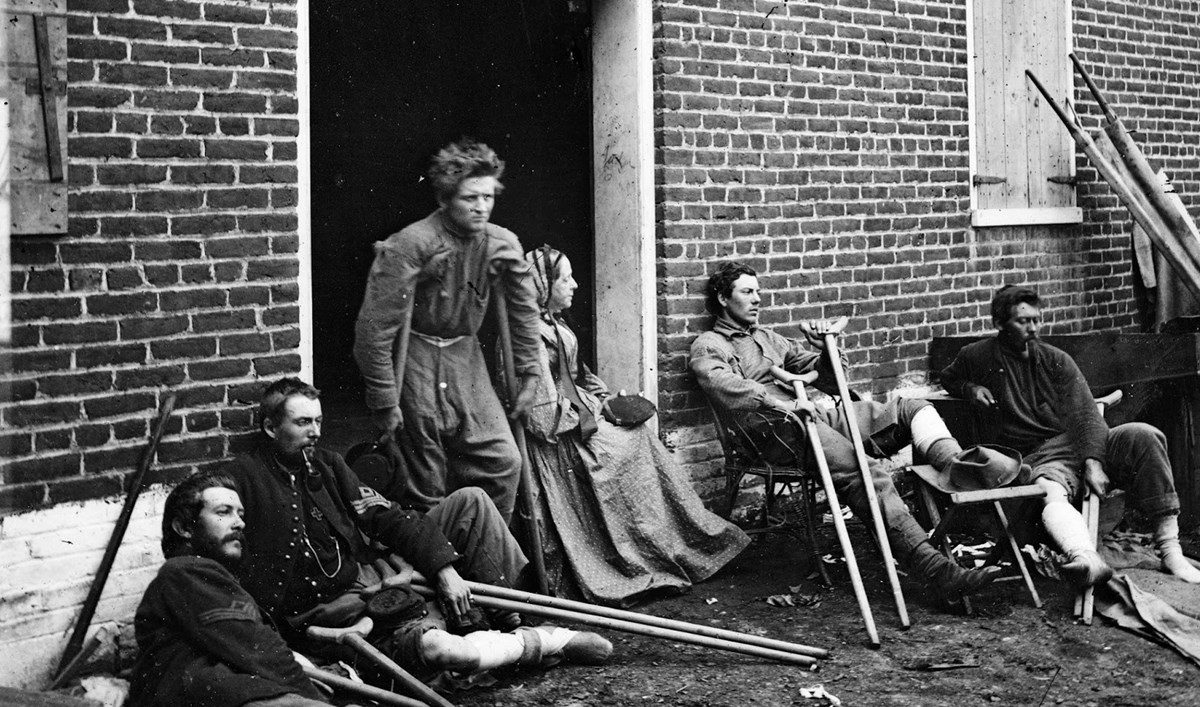 Wounded soldiers resting outside the Sanitary Commission depot in Fredericksburg, 1864. One woman is seated in doorway