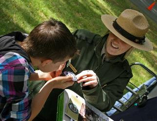 NPS Ranger presents child with Junior Ranger patch