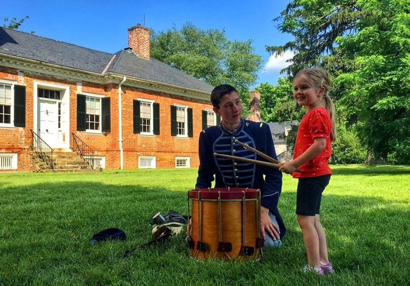Child plays drum during living history event under supervision of Union drummer with Chatham Manor in background