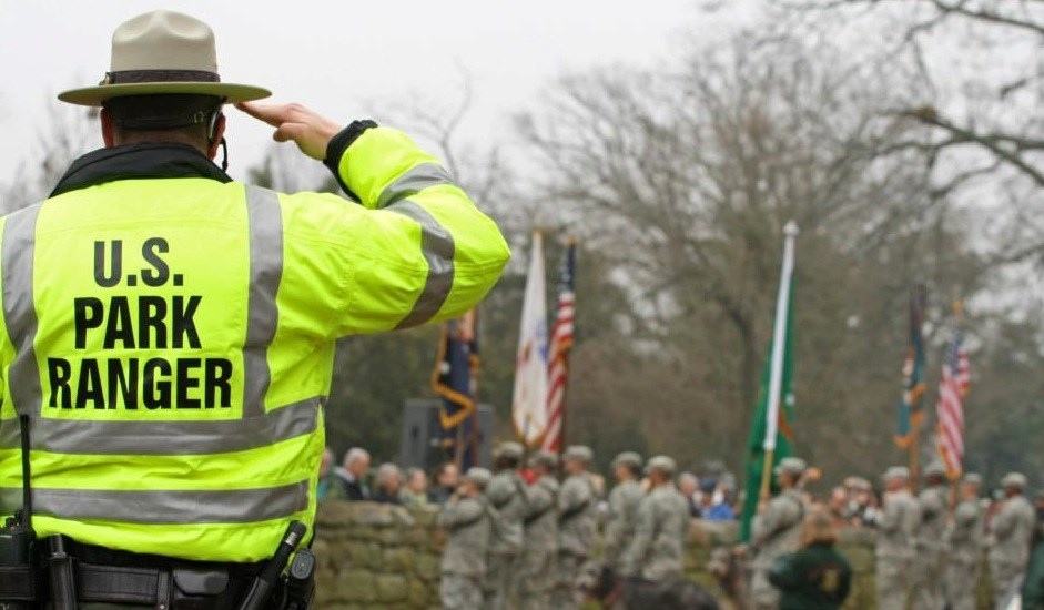 Park law enforcement ranger in yellow best saluting during 150th anniversary commemoration on the Sunken Road