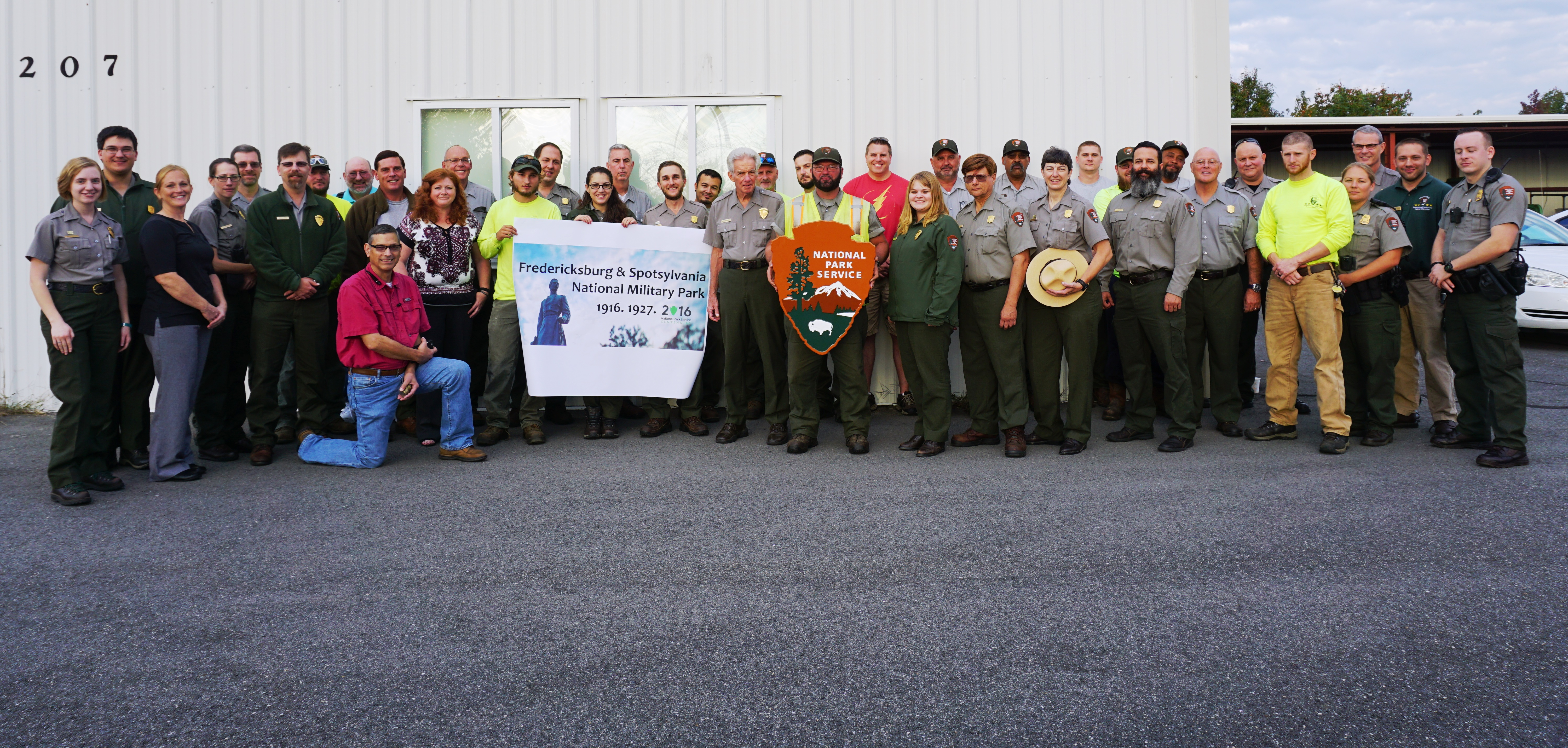 Entire park staff posing for a photo with arrowhead and white banner