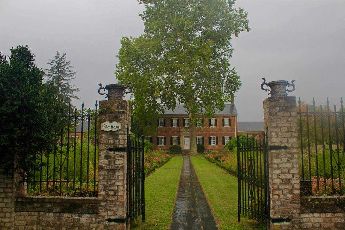 Large brick Georgian-style house and garden with stormy sky in background