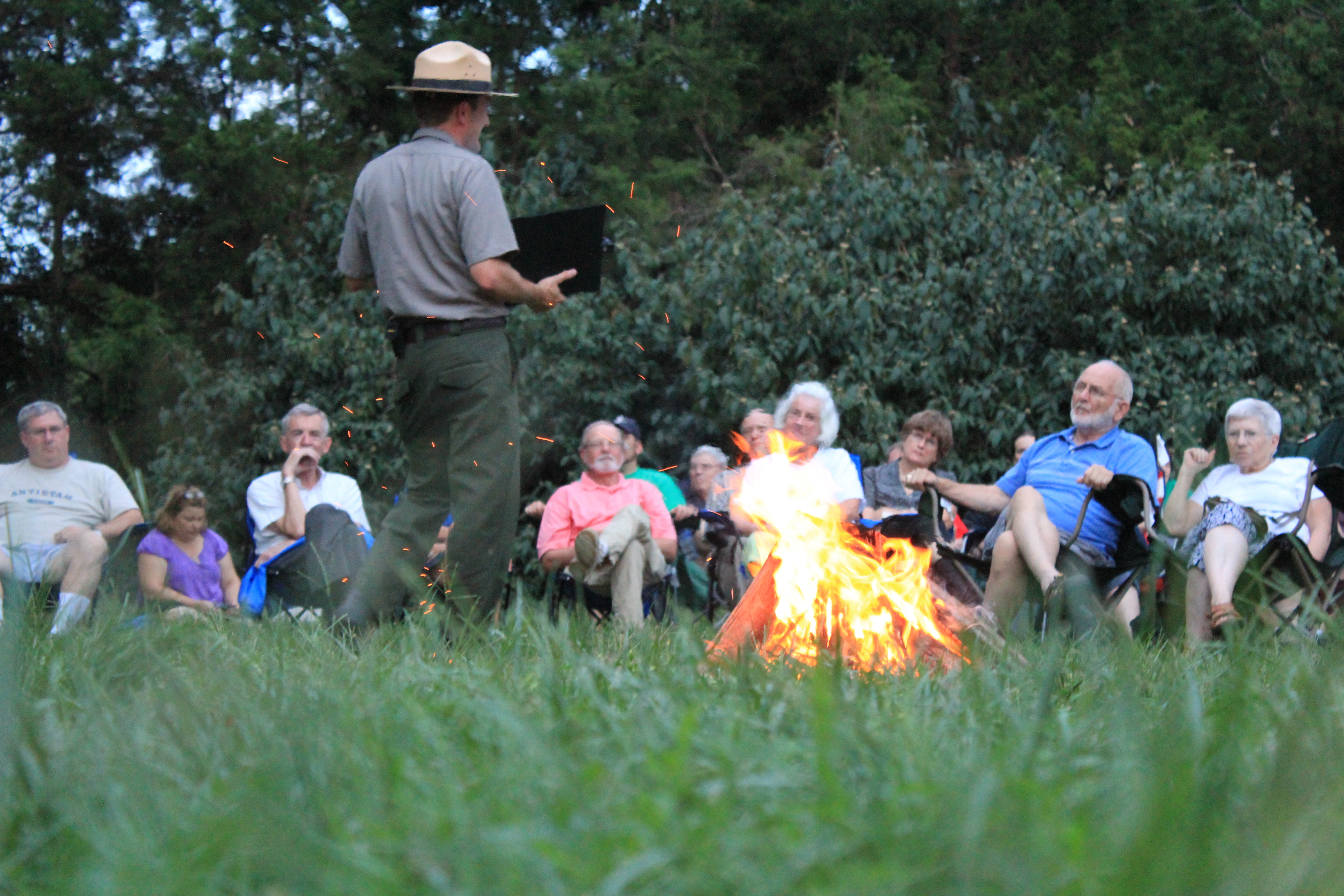 Ranger talks next to a blazing campfire with audience in the background