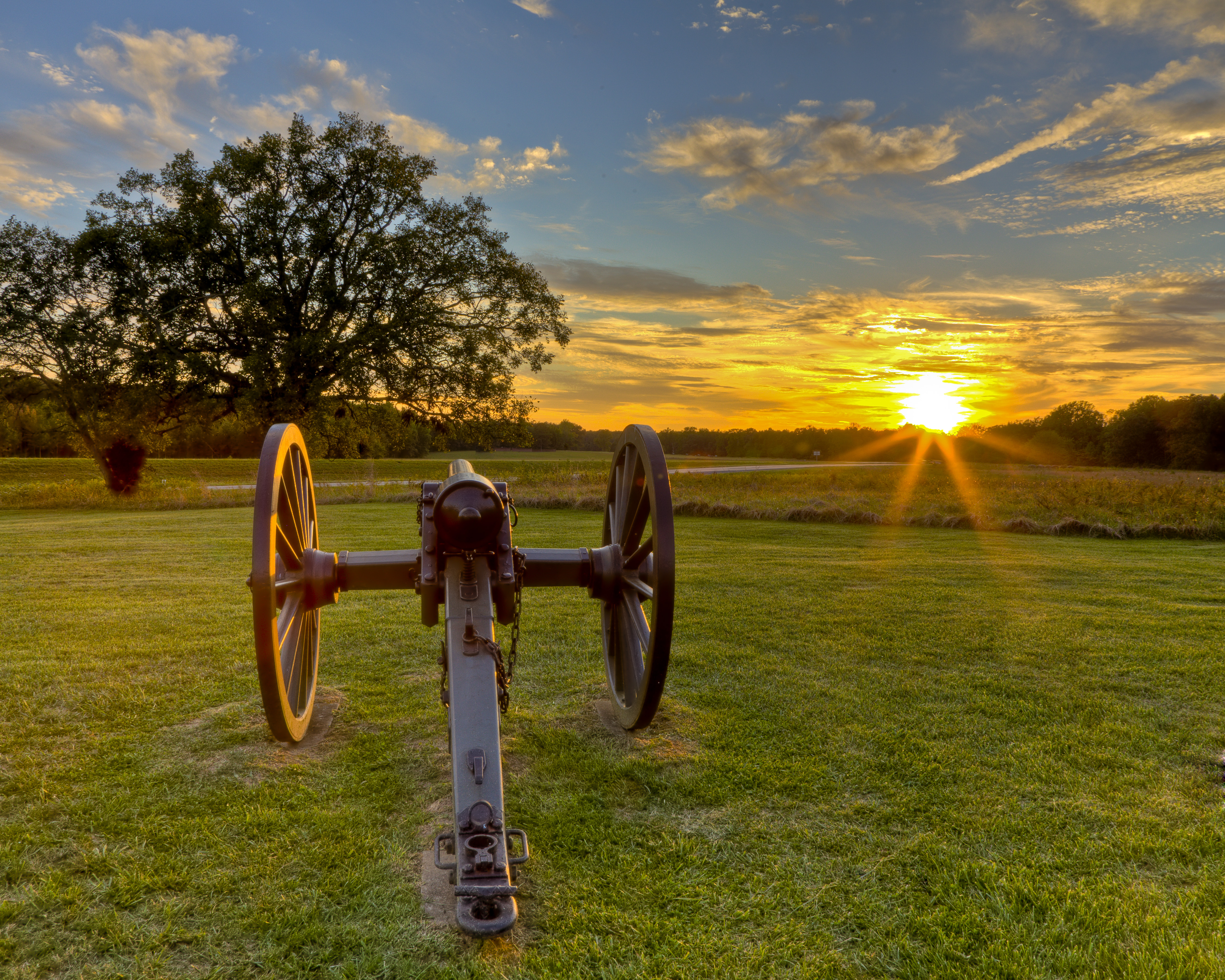 Cannon in front of fields with distant tree line and sun setting in background