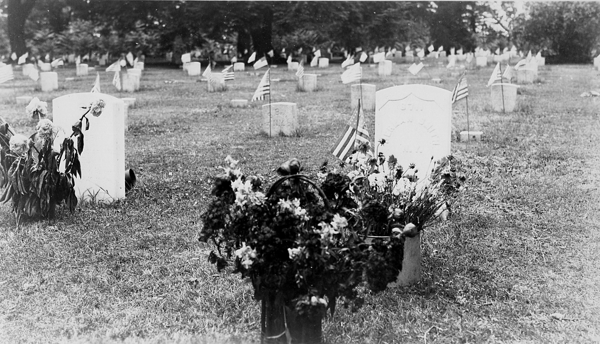 Black and white photo of graves in national cemetery with flowers in front